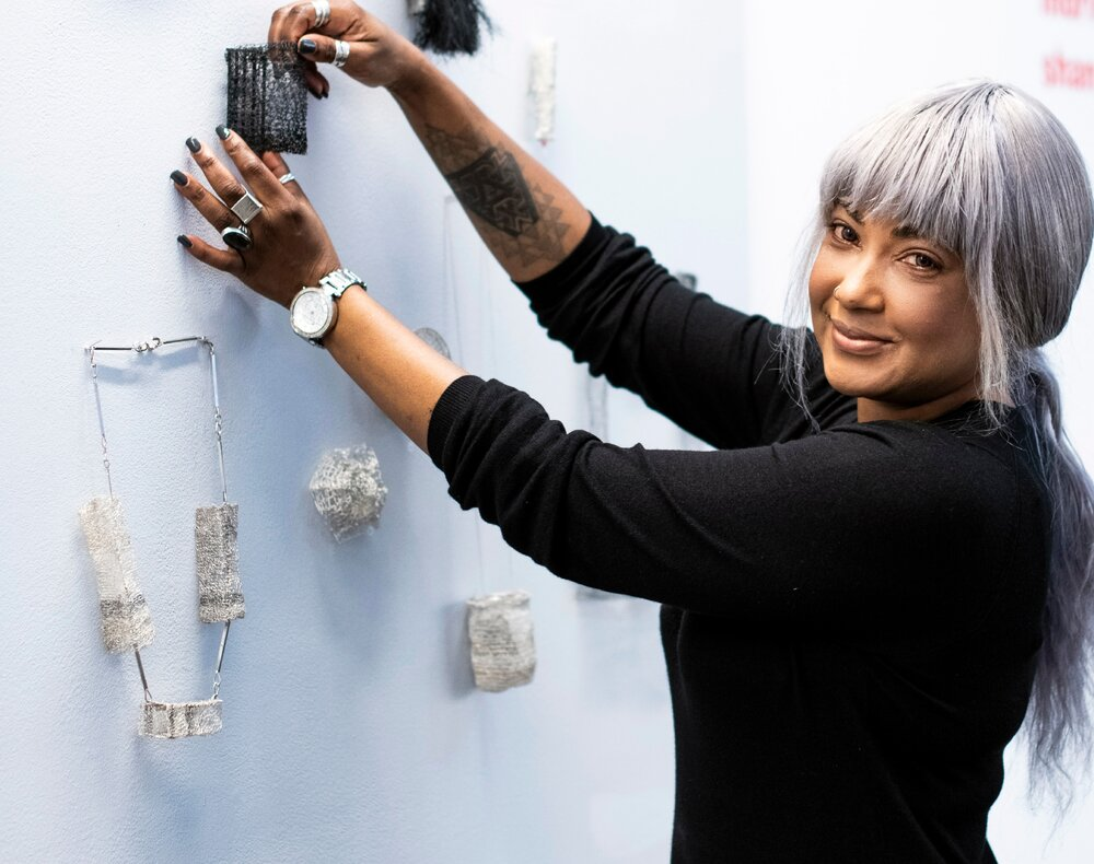 A photograph of Cat Dunn hanging some of her design work on a wall