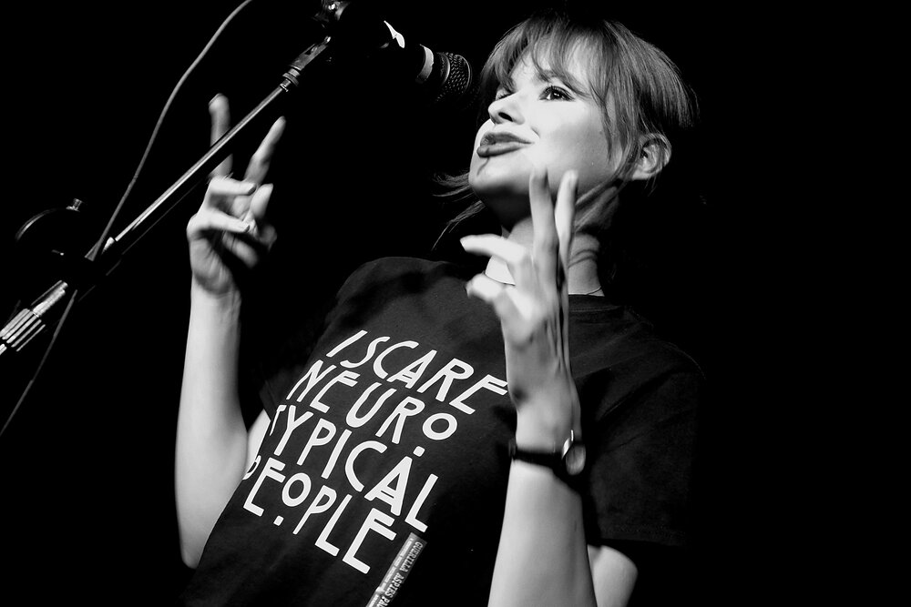 black and white profile photo of Hannah on stage performing and making hand gestures.