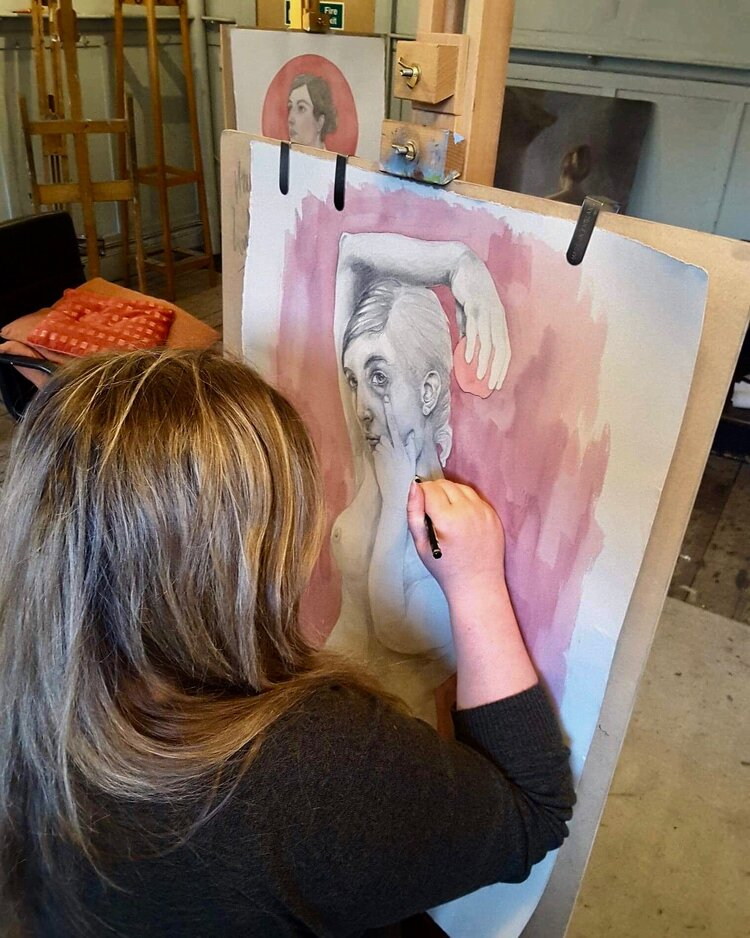 Hannah Lyth with her back to the camera working on a figurative painting.