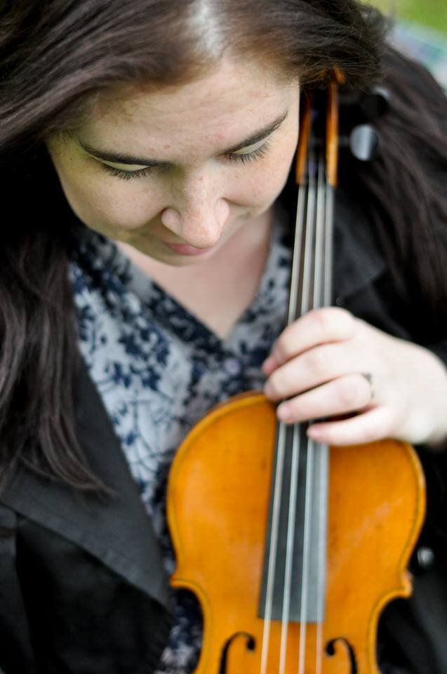 profile photo of eilidh steel lookin down towards the fiddle she is holding.