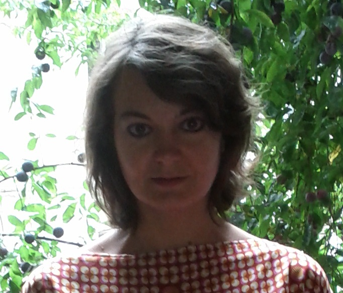 profile photo of francesca facing towards the camera with foliage in the background.