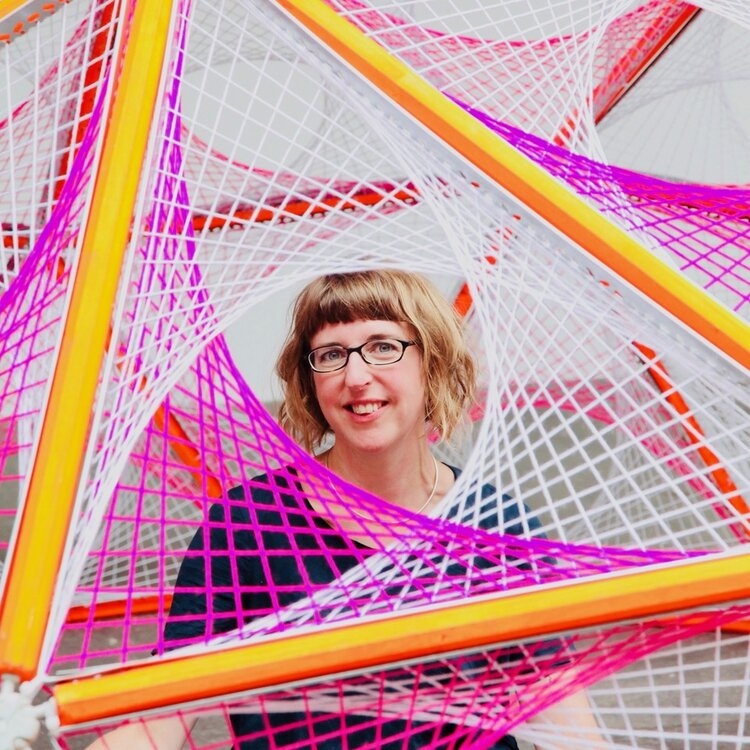 Hannah Ayre looking through lare sculpture installation in pink, yellow and white woven material.