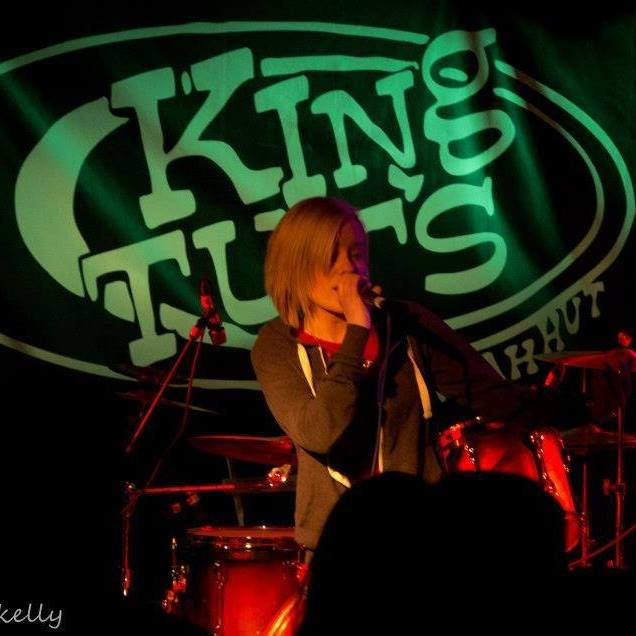 emma performing on a tage with king tuts venue logo in background.