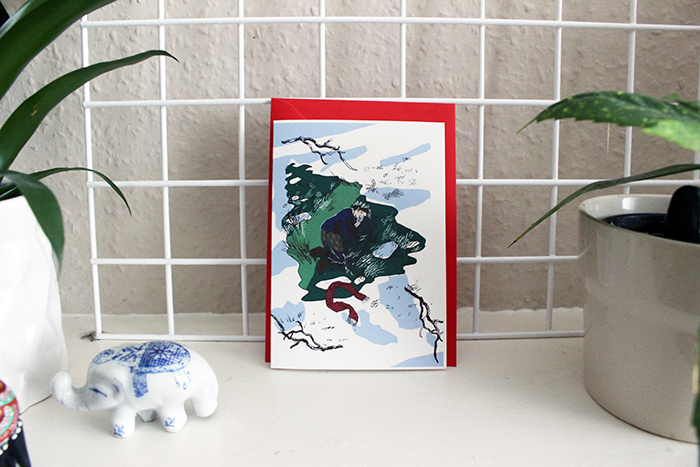 an illustrated card with blue and green watercolour drawing and red envelope propped up on tiled wall with plants on each side.