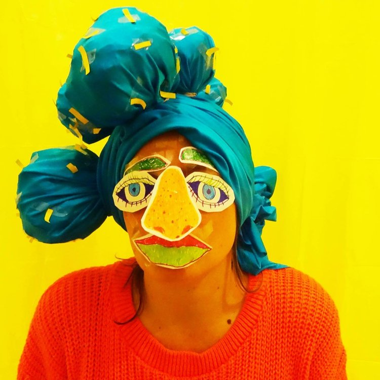 Greeer Pester against a yellow background with bright turquoise headscarf and cut out collage face mask.