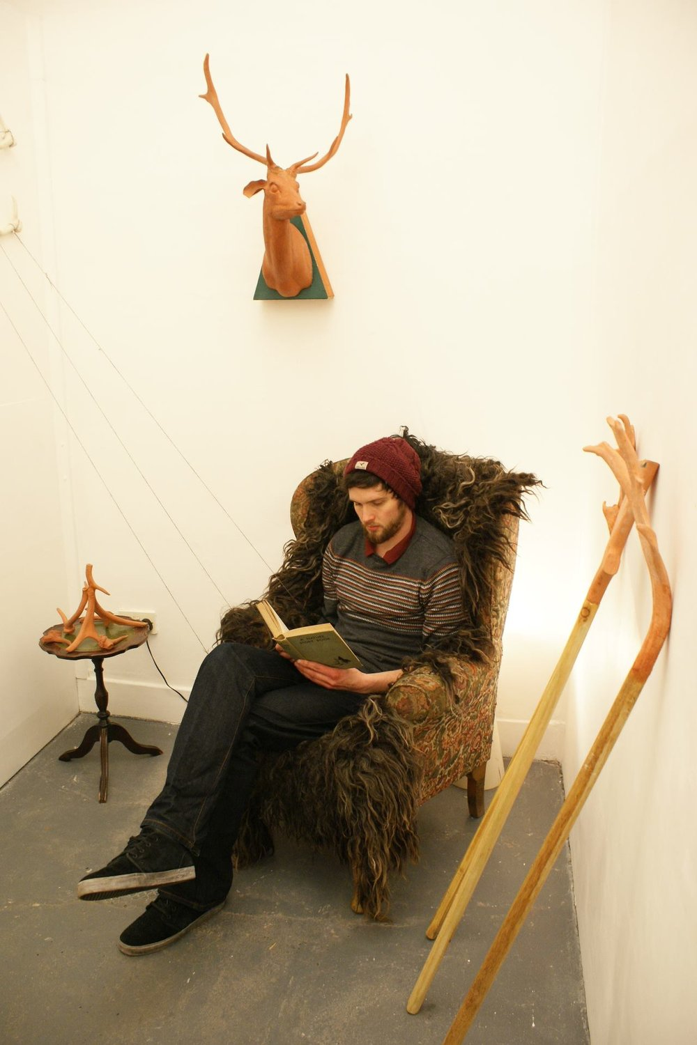 image of Kevin sitting reading on a chair.