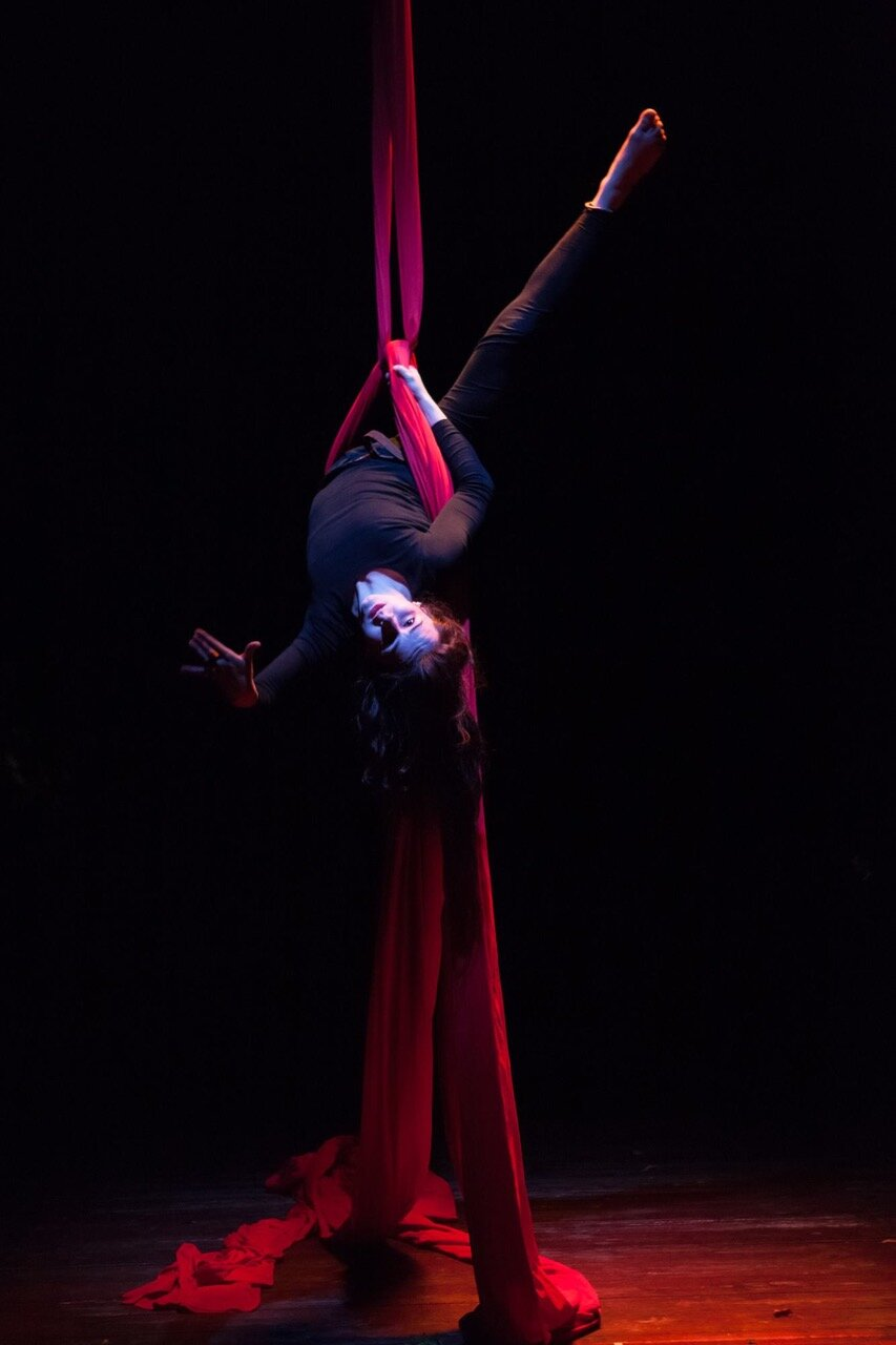Katarzyna performing on silk ties in an acrobatic position against a black background.