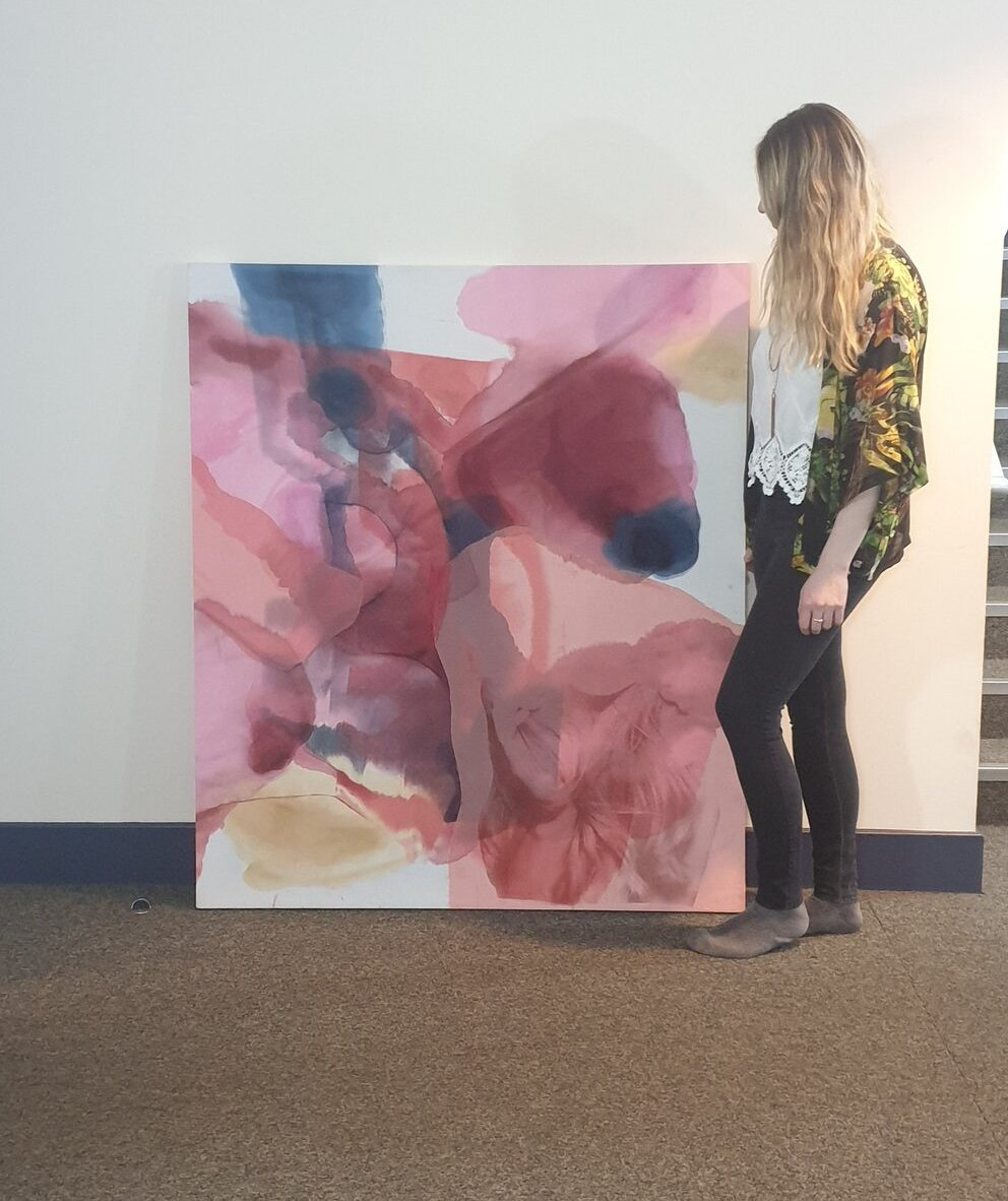 photograph of jade standing next to one of her large abstract paintings in pink tones looking down towards it.