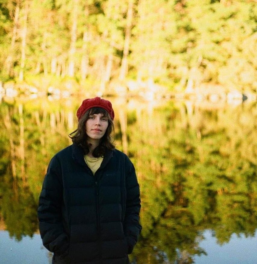 Jeanne hamilton standing outside in front of a pond with trees in background.