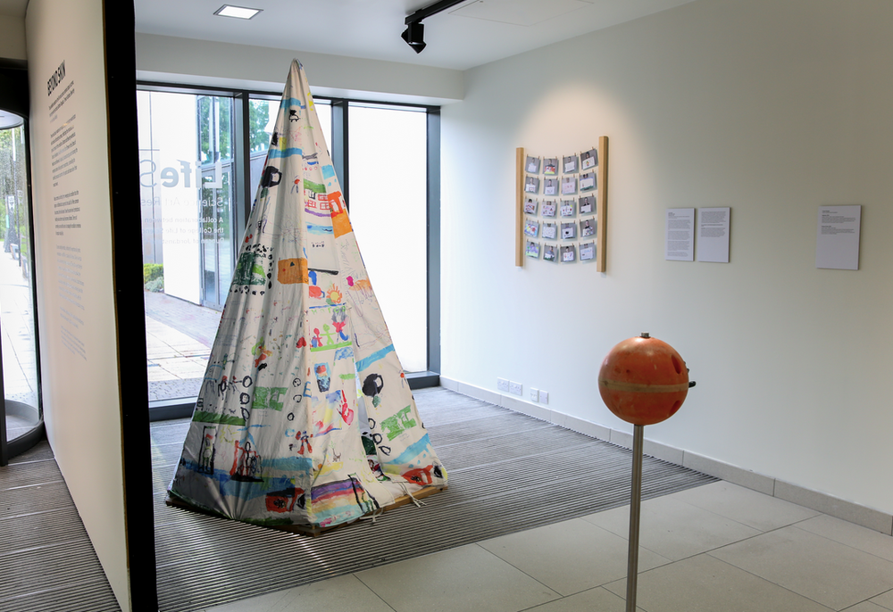 installation view of various design objects including multicoloured tent and wall hanging.