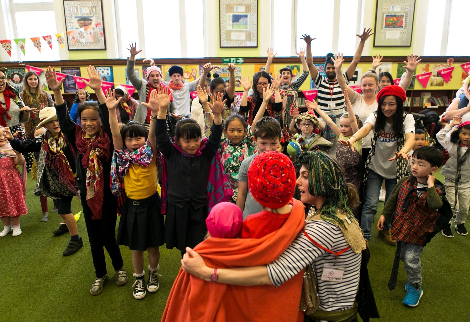 workshop with lots of children and young people waving arms in the air and dressed in costume.