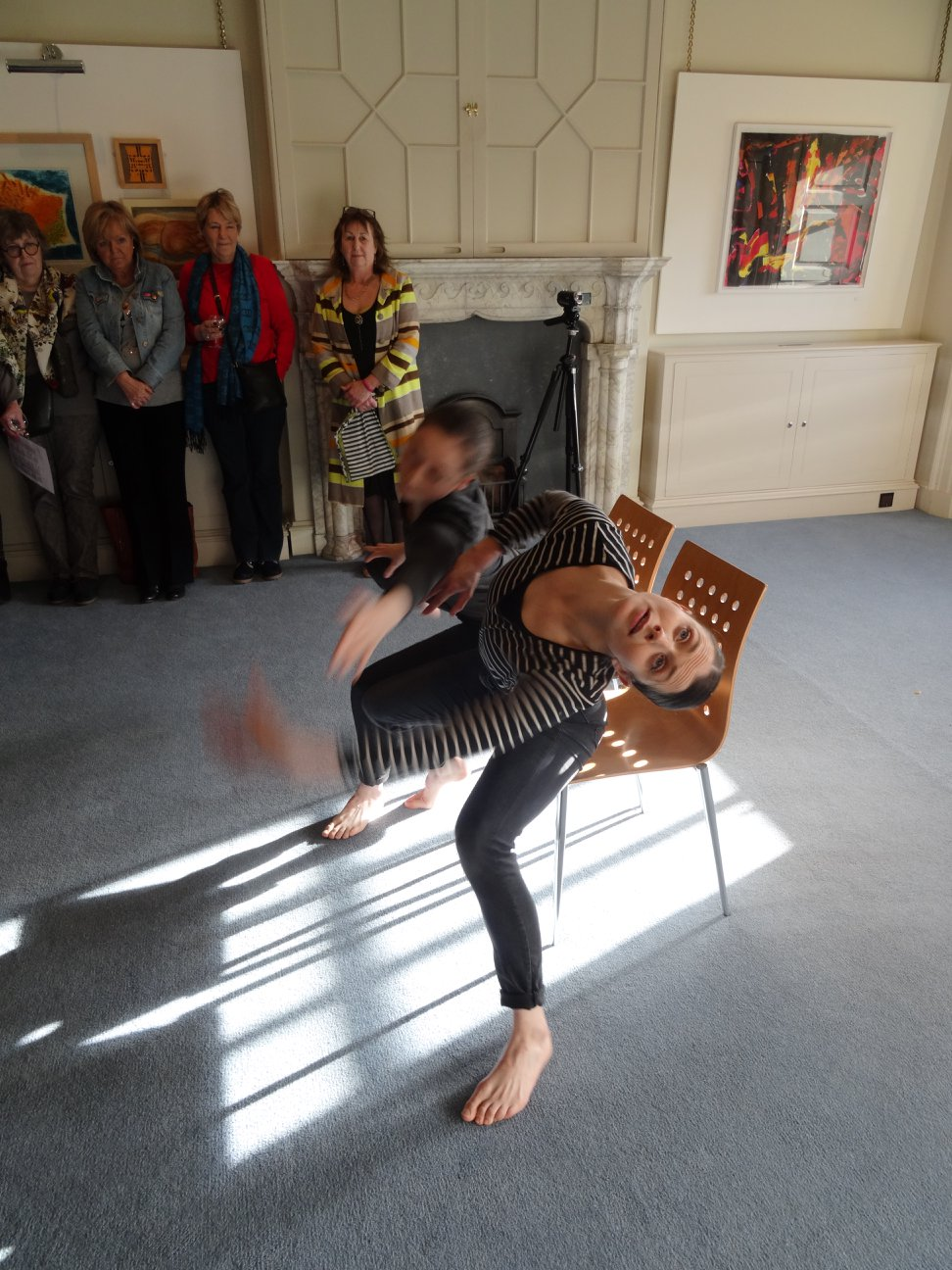 people in a room with two people in middle doing a performative dance.