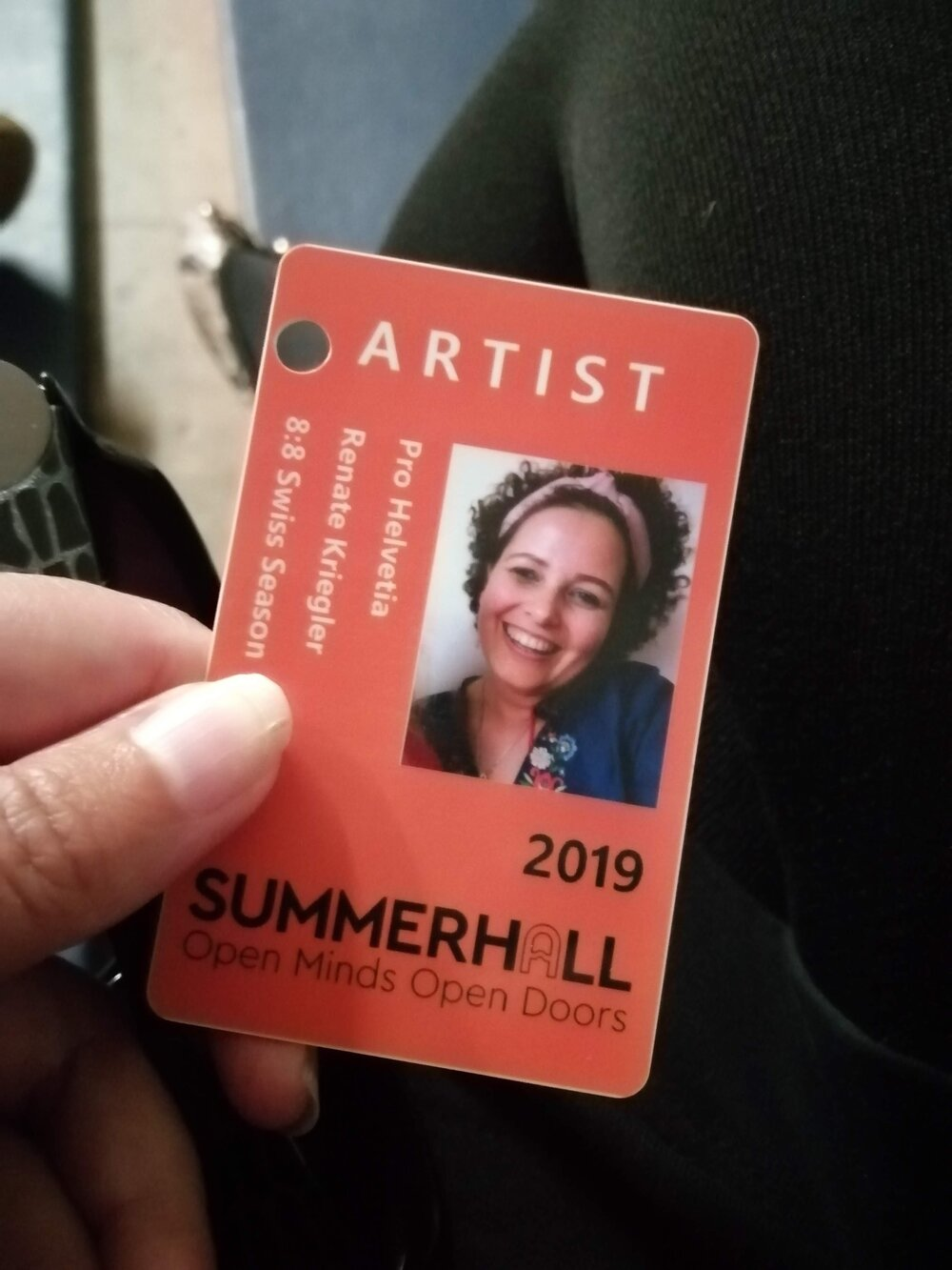 image of hand holding up Renate's ID pass with 'artist' at the top.