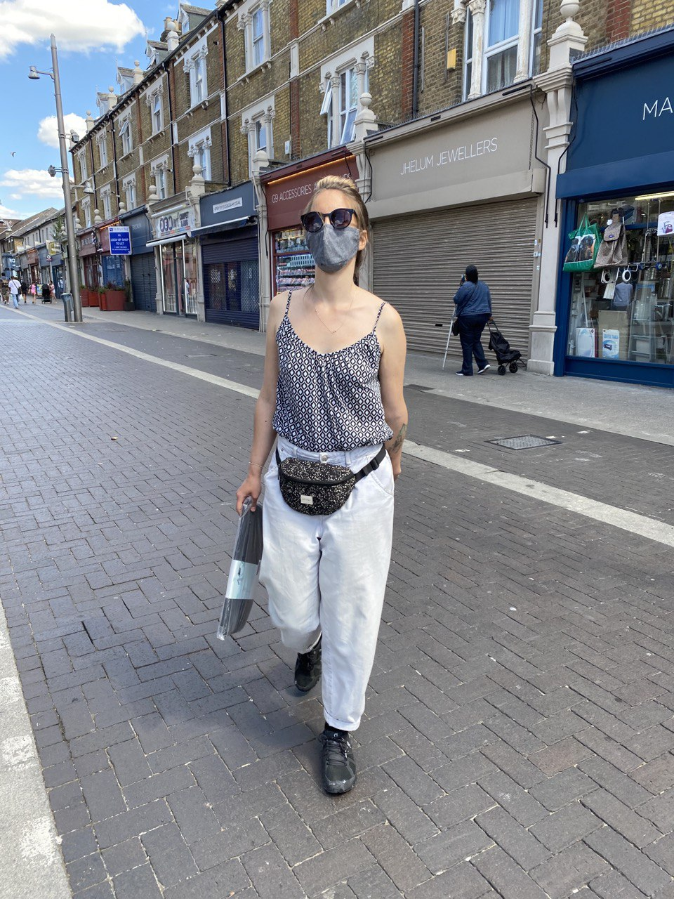 profile image of Adriana wearing a mask standing on the street.