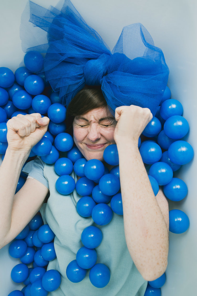a performance taking place, a person with their fists clenched surrounded by blue fabric and balloons.