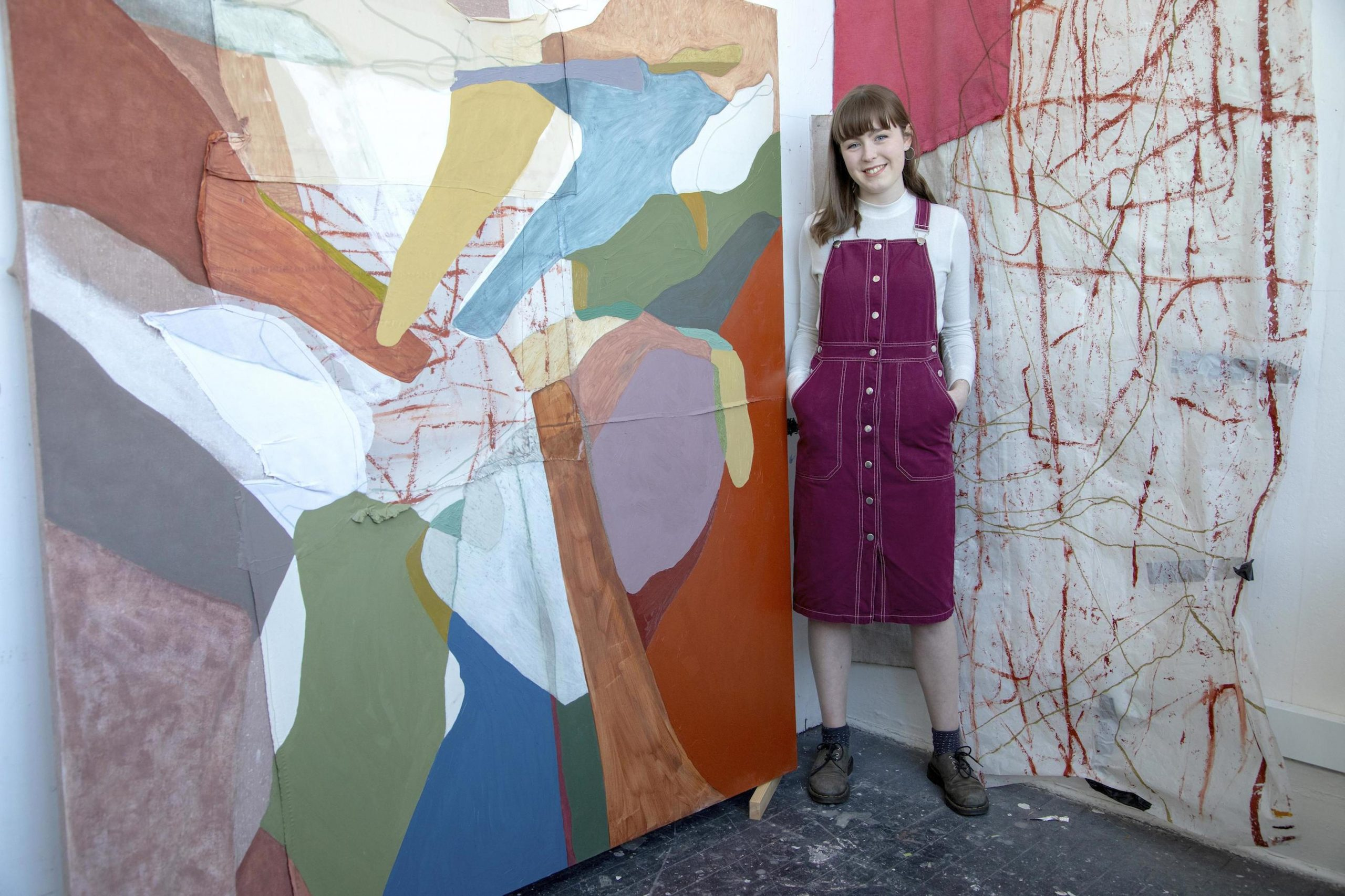Siobhan standing next to one of her paintings.