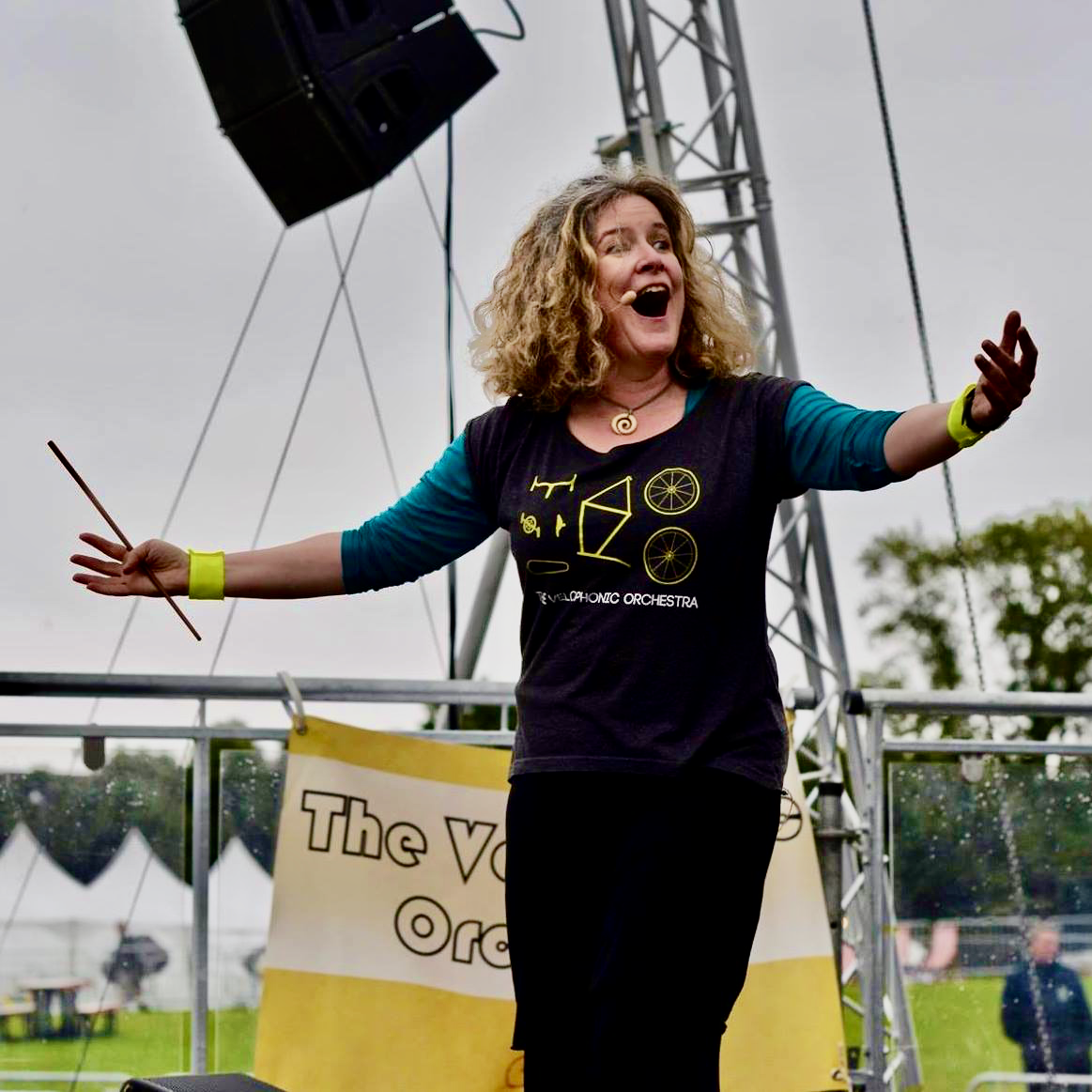 Jane Bentley on stage performing at an outdoor event.