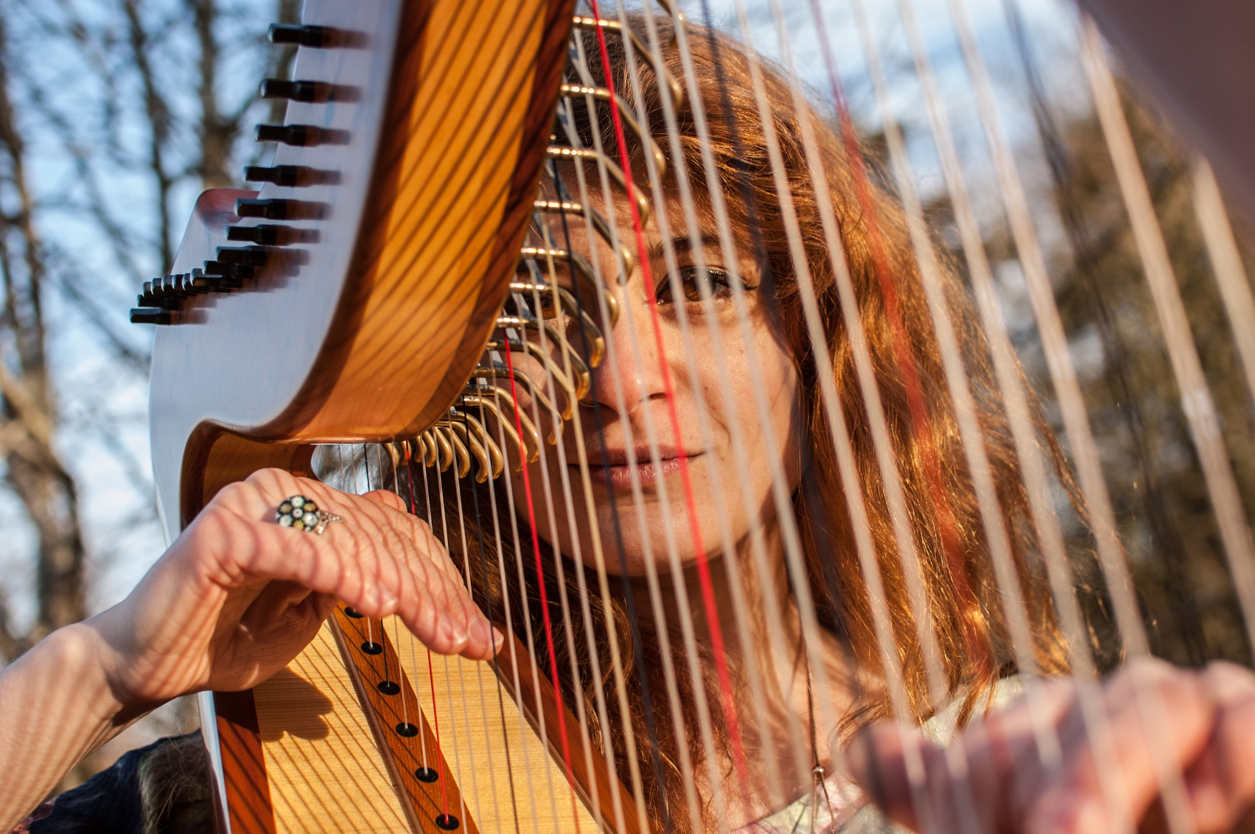 Sam MacAdam posing behind the strings of her harp.