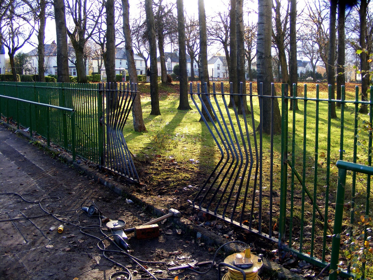 a wooded area with a fence which has been bent to create a gap from the pavement.