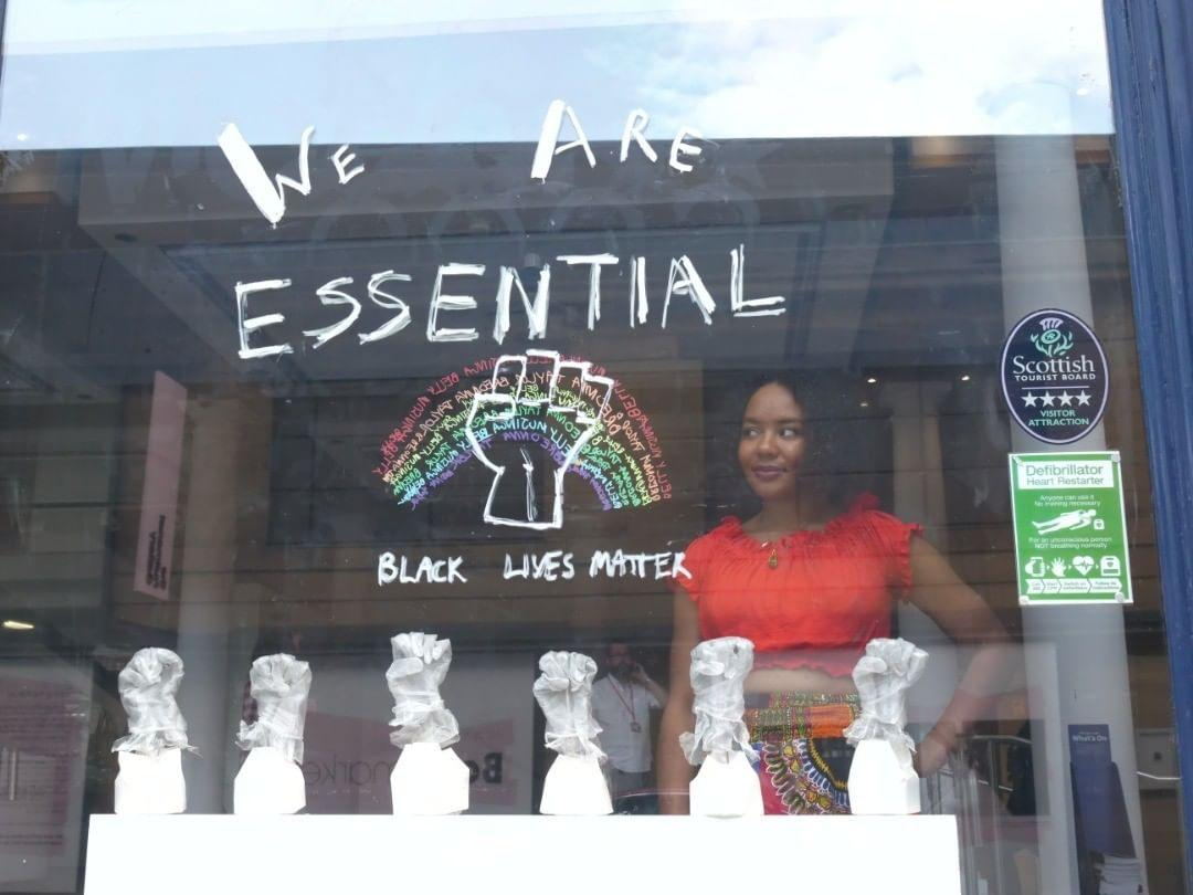 libby standing behind a window display which shows a line of sculpted fists and writing above which says 'we are essential, black lives matter' and a rainbow.