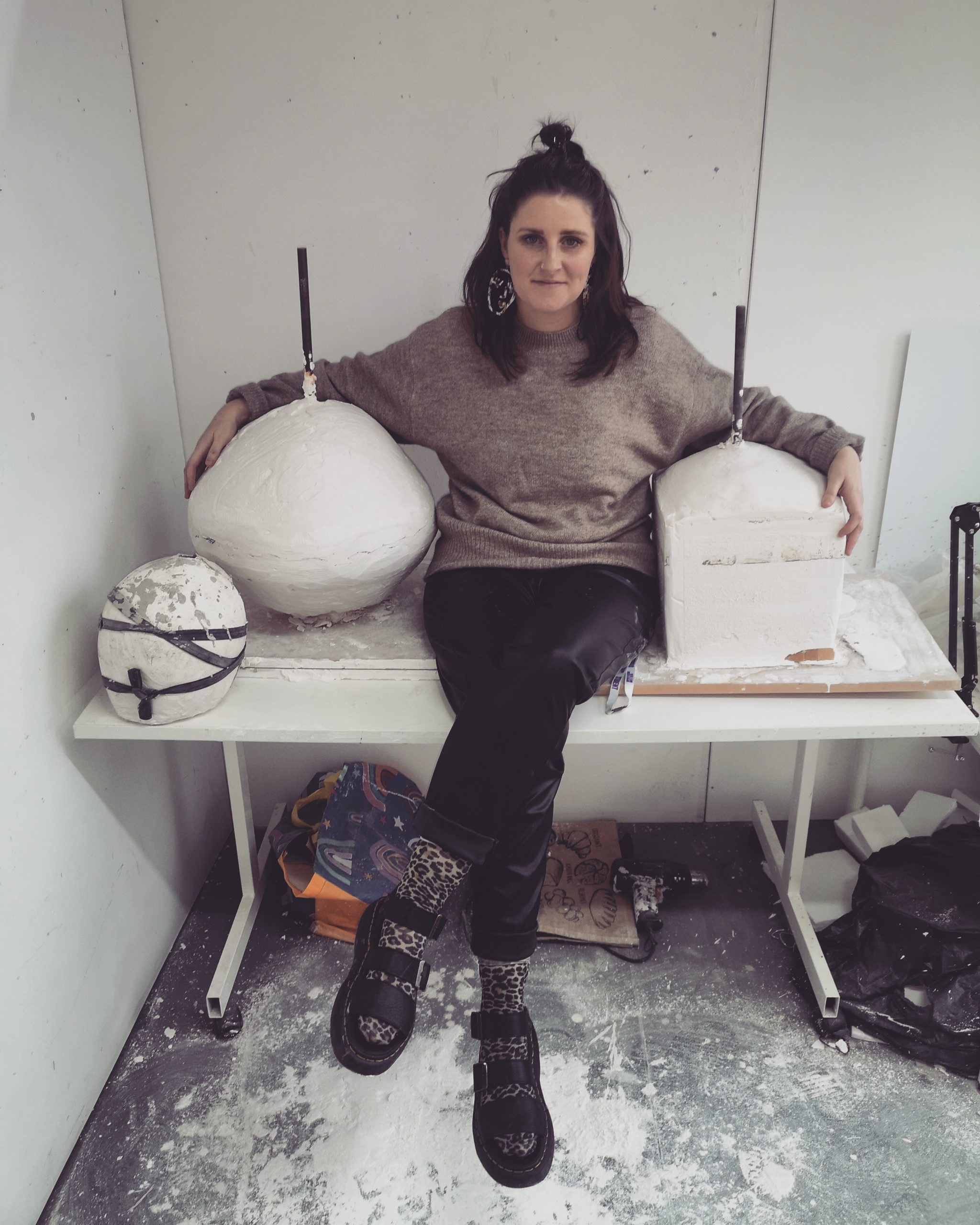 Lynsey sitting on a table in a sculpture workshop surrounded by clay items.