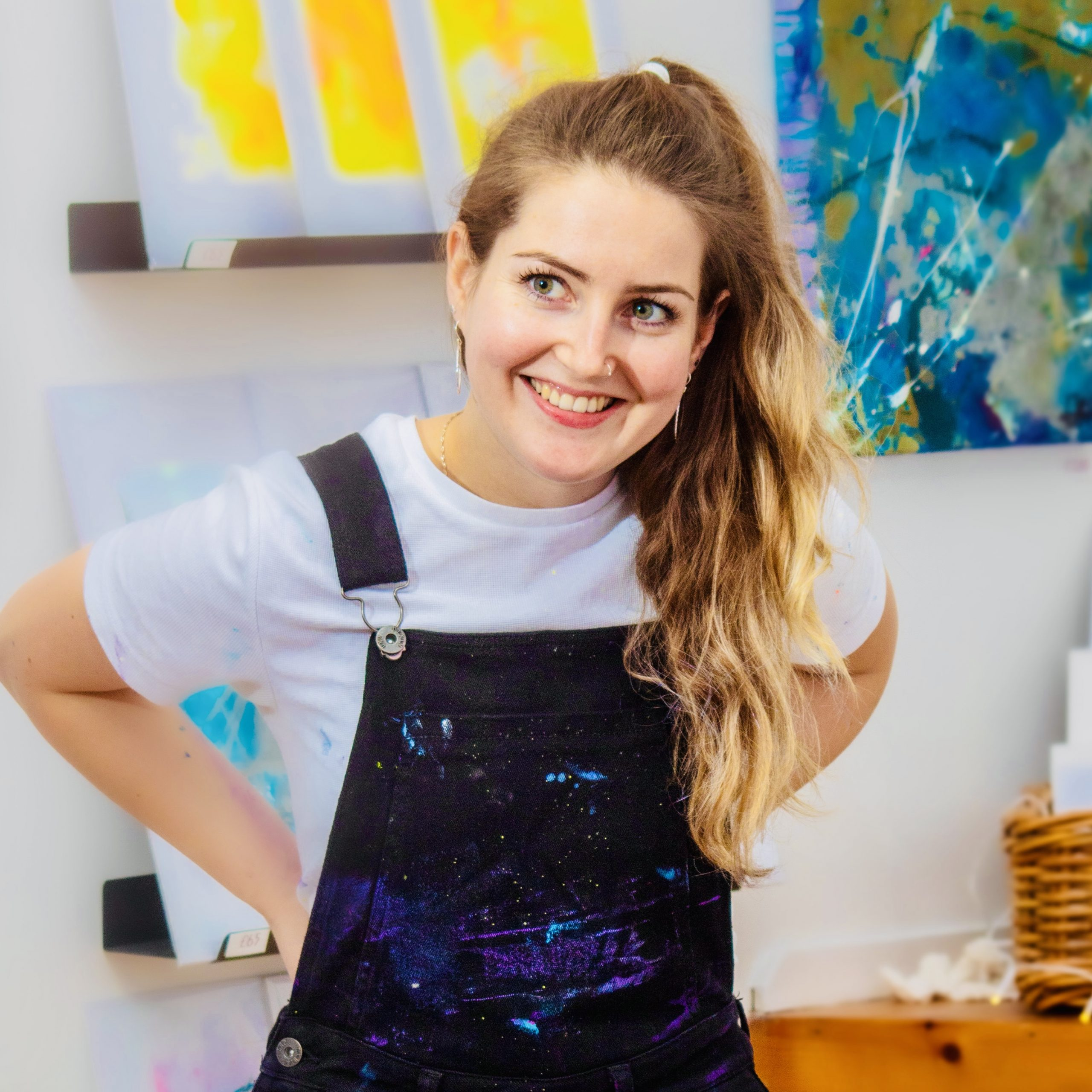 profile image of Kayleigh with bright and colourful paintings behind her.