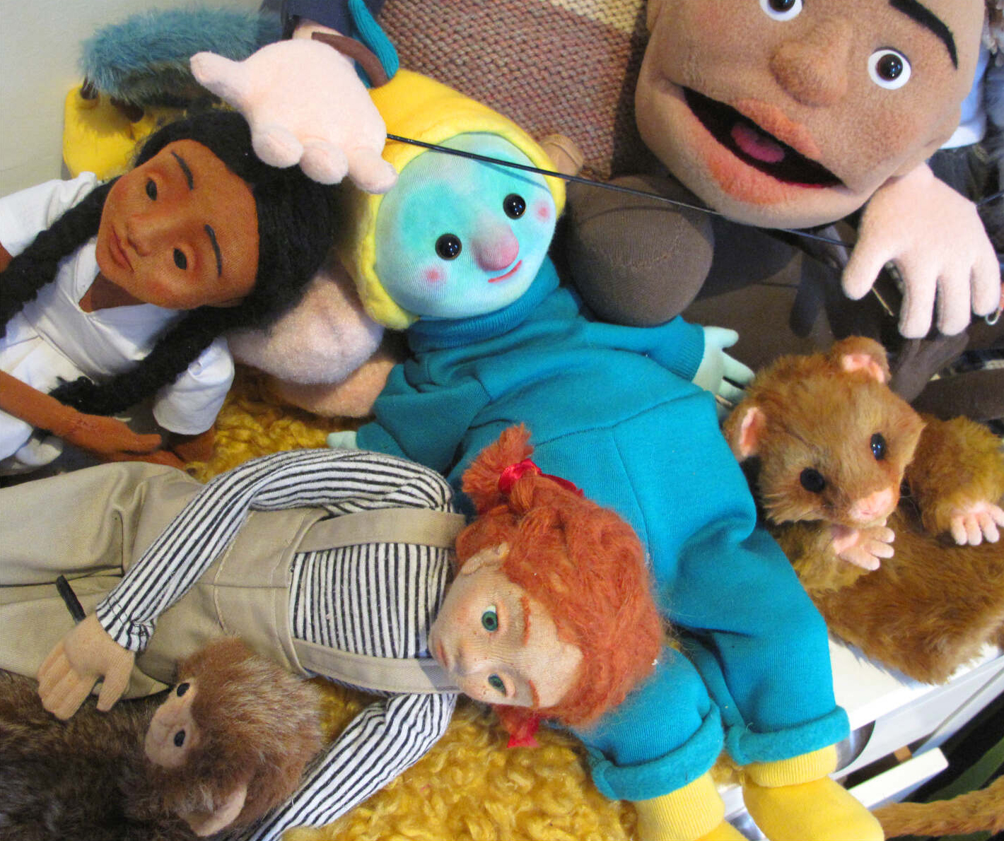 a pile of puppets of all different shapes, sizes and colours. Some look like animals and some look like humans.