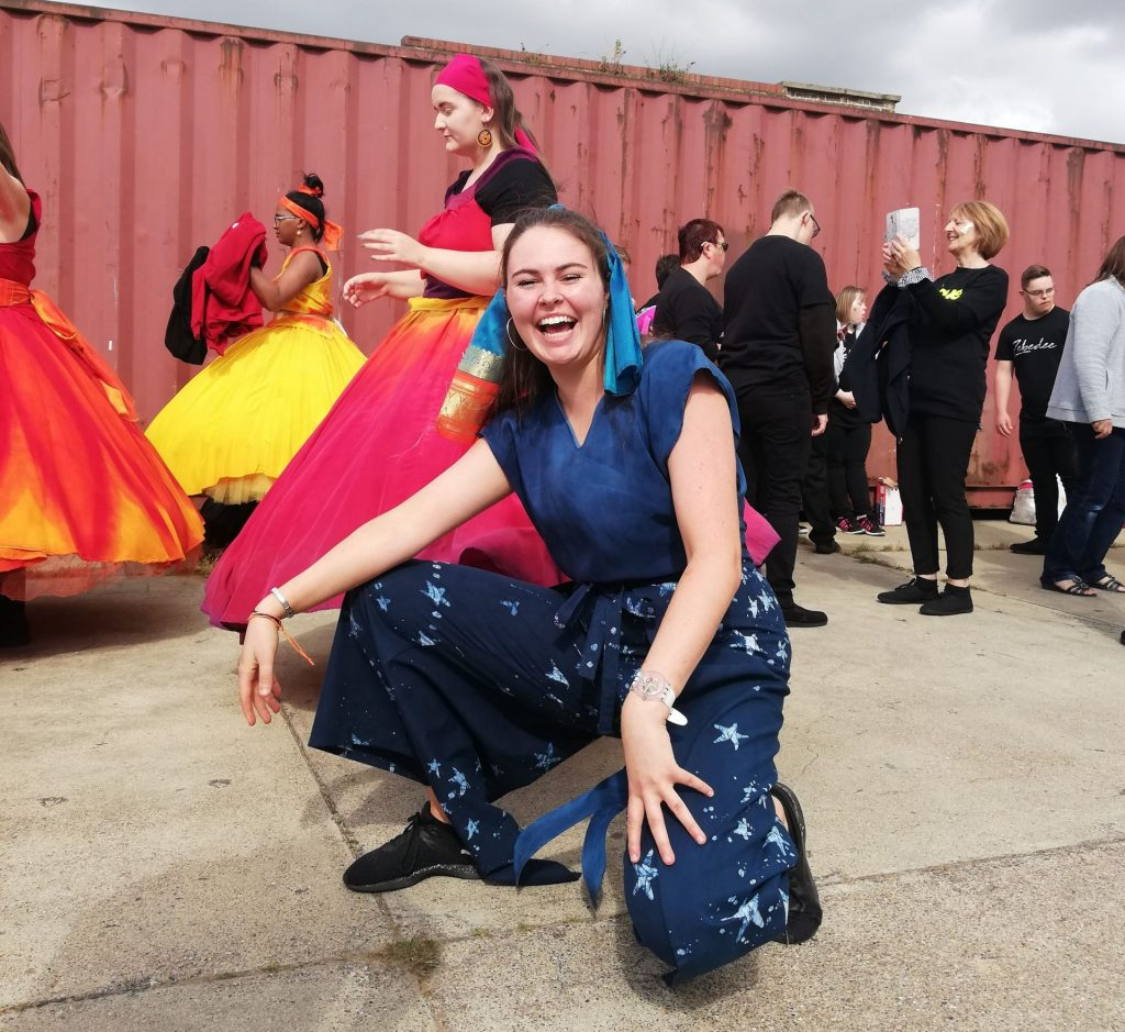 Profile image of Sally Hendry, Company DNA Director, crouching in front of a shipping container with people in costume behind her.