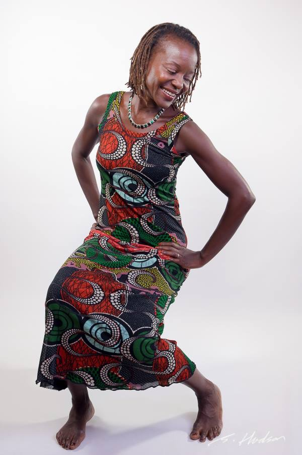 Selma in a brightly coloured pattered dress in the middle of a dance pose.