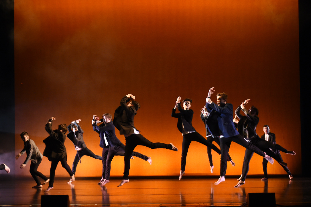 a group of dancers on stage wearing black clothing against a dusty orange backdrop.