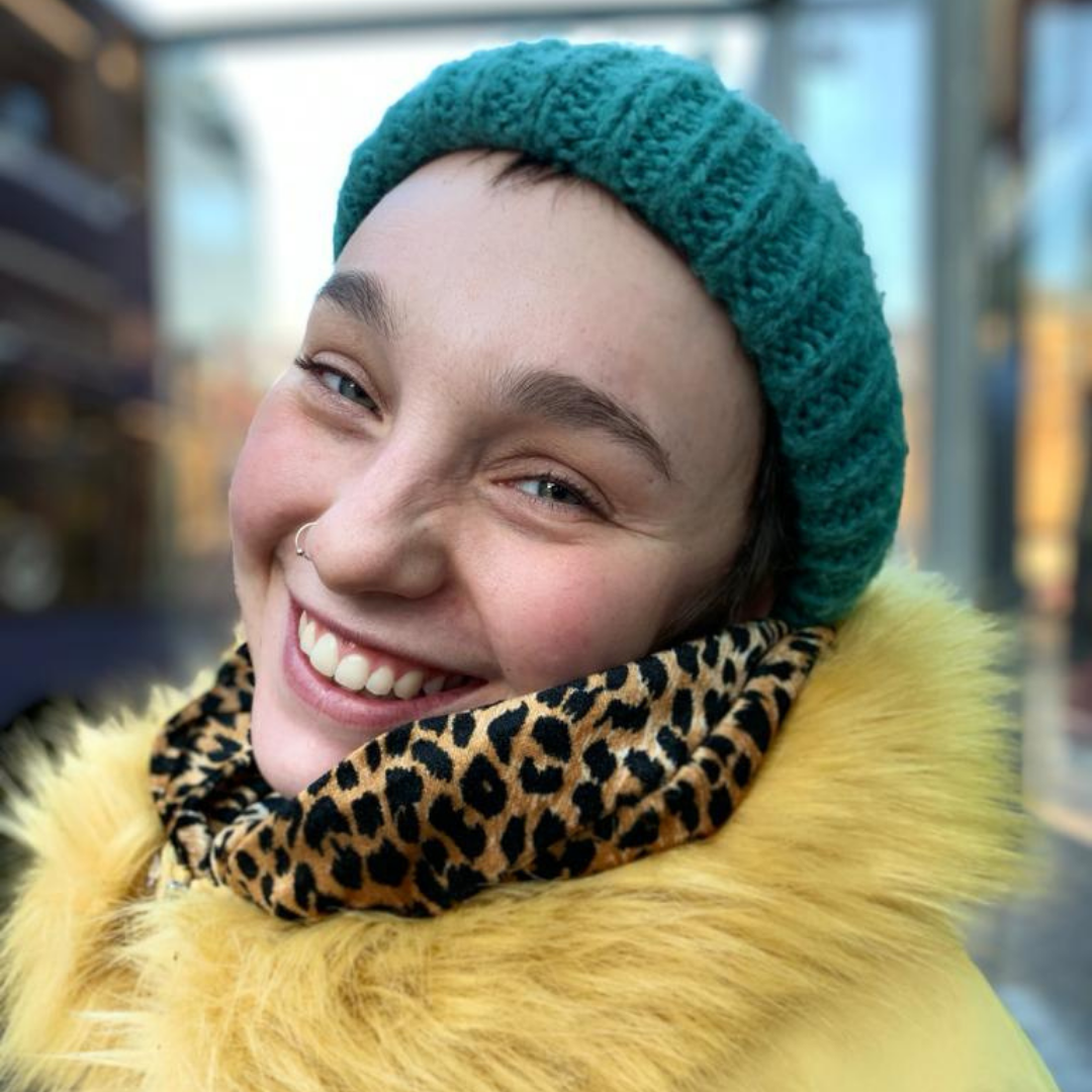 Profile Image of Rebecca wearing a bright yellow jacket and green hat.