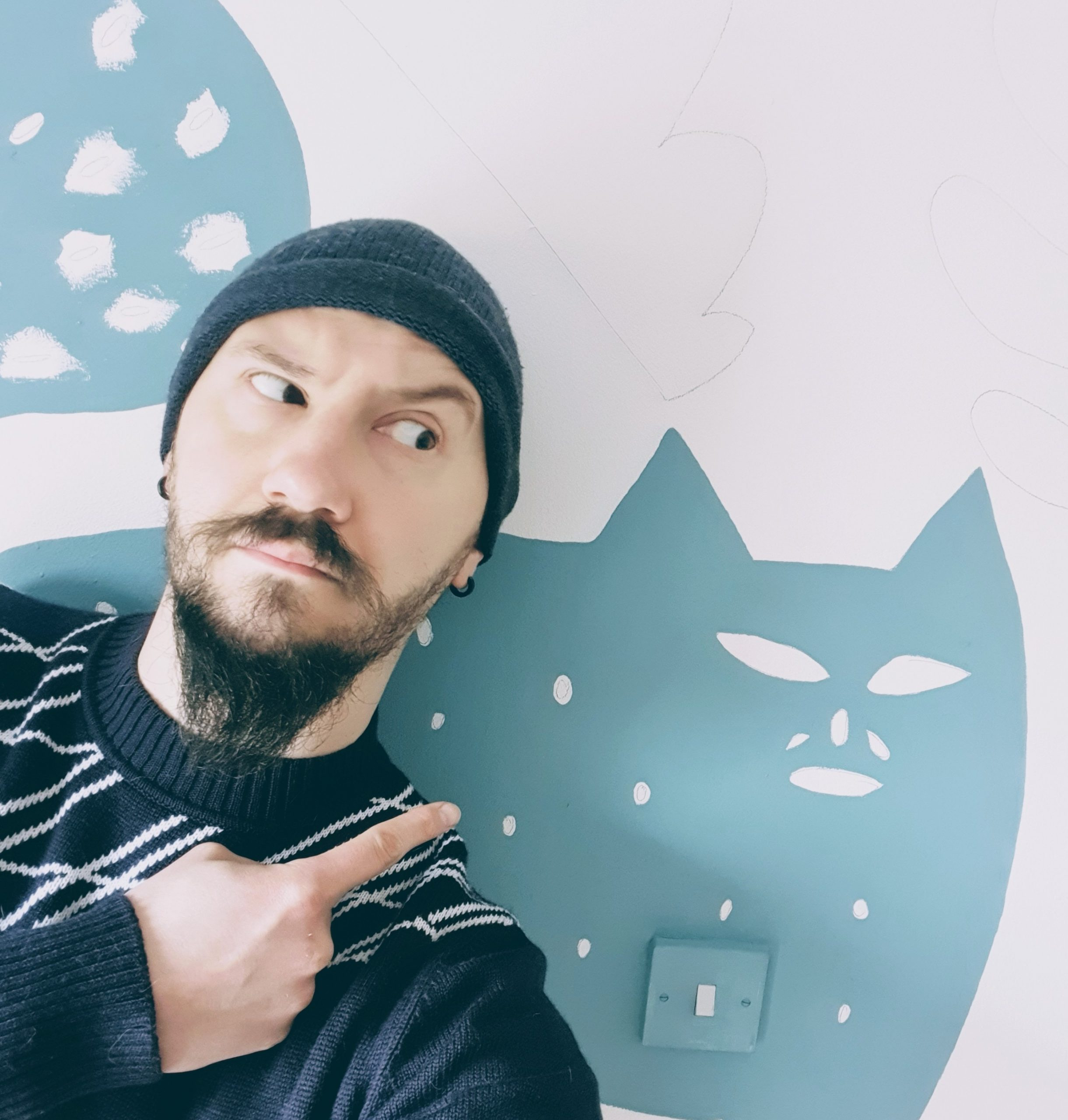 image of Filip pointing behind him to a wall mural of a blue cat.