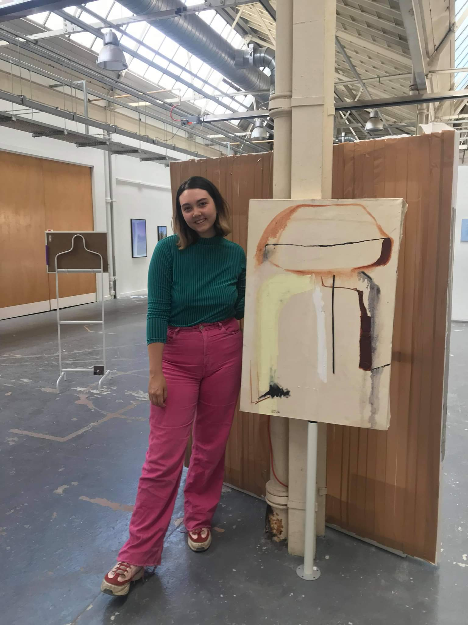 Profile image of Sam Harley standing next to one of their abstract paintings.