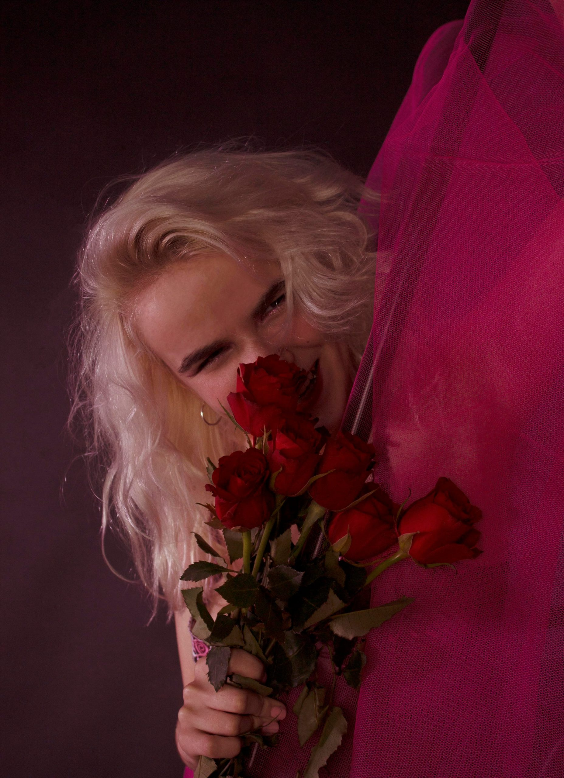 Profile image of Caitlin Macleod with bright blond hair and face partially obscured behind a bunch of red roses.